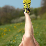 closeup of male stretching leg with yellow running shoe outdoors